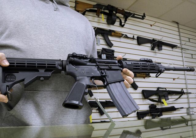 John Jackson, co-owner of Capitol City Arms Supply shows off an AR-15 assault rifle for sale Wednesday, Jan. 16, 2013 at his business in Springfield, Ill.