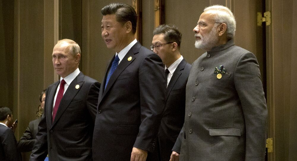 (L to R) Russian President Vladimir Putin, Chinese President Xi Jinping and Indian Prime Minister Narendra Modi arrive for the Dialogue of Emerging Market and Developing Countries on the sidelines of the 2017 BRICS Summit in Xiamen, southeastern China's Fujian Province on September 5, 2017