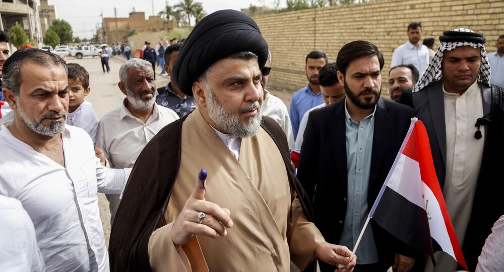 Iraqi Shiite cleric and leader Moqtada al-Sadr (C-L) shows his ink-stained index finger and holds a national flag while surrounded by people outside a polling station in the central holy city of Najaf on May 12, 2018 as the country votes in the first parliamentary election since declaring victory over the Islamic State (IS) group