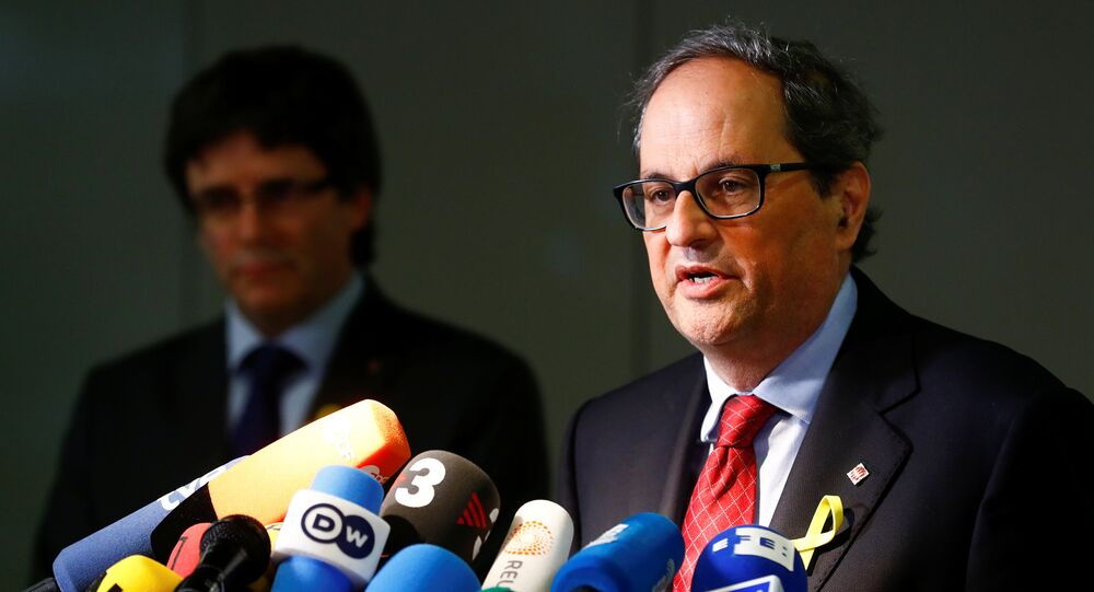 Newly elected regional leader of Catalonia Quim Torra (R) and his predecessor Carles Puigdemont attend a news conference in Berlin, Germany May 15, 2018