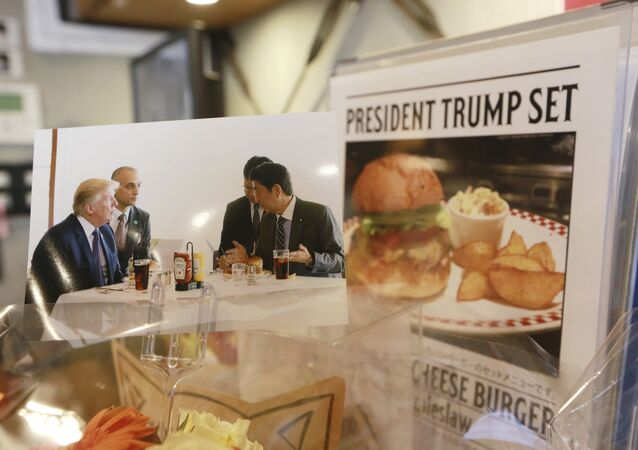 A photo showing U.S. President Donald Trump, left, and Japanese Prime Minister Shinzo Abe, right, at a lunch of hamburgers from Munch's Burger Shack at Kasumigaseki Country Club, is displayed at the burger restaurant in Tokyo Thursday, Nov. 16, 2017