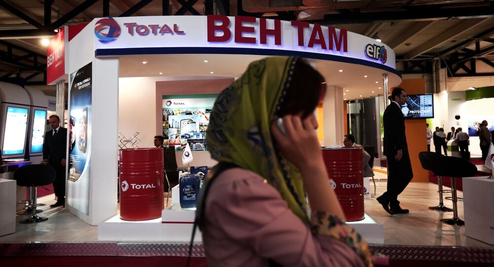 A South Korean businesswoman speaks on her mobile phone in front of the stand of French oil and gas company Total, at Iran's annual International Oil, Gas, Refining & Petrochemical Exhibition in Tehran, on May 6, 2014