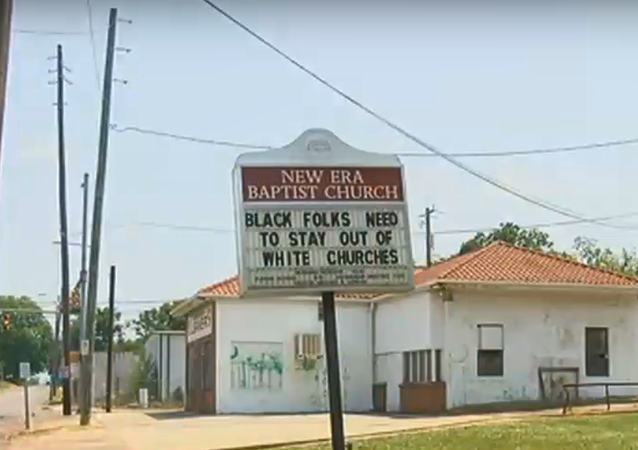 New Era Baptist Church in Birmingham, Alabama, with sign reading Black folks need to stay out of white churches and  White folks refused to be our neighbors, May 12, 2018