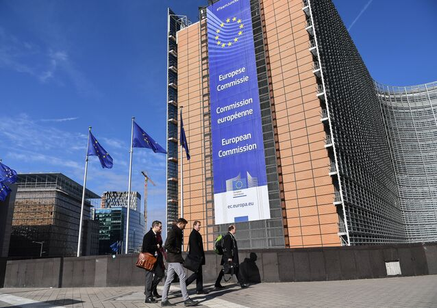 A picture taken on March 14, 2018 shows European Union flags next to the European Commission headquarters in Brussels, adorned by a banner displaying its name in French, amongst others European languages