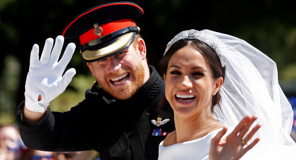 Britain's Prince Harry and his wife Meghan wave as they ride a horse-drawn carriage after their wedding ceremony at St George's Chapel in Windsor Castle in Windsor, Britain, May 19, 2018