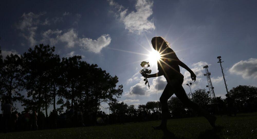 Hannah Harrison carries roses during a prayer vigil following a deadly shooting at Santa Fe High School in Santa Fe, Texas, on Friday, May 18, 2018