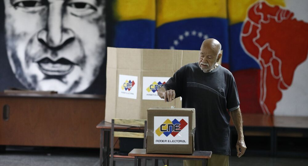With an image of the late Venezuelan President Hugo Chavez behind him a Venezuelan citizen casts his vote at a polling station during the presidential election in Caracas, Venezuela, May 20, 2018