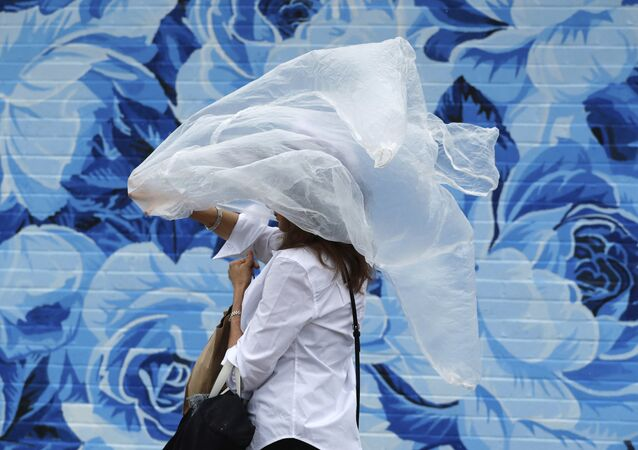 A woman puts on a plastic cover before the 144th running of the Kentucky Derby horse race