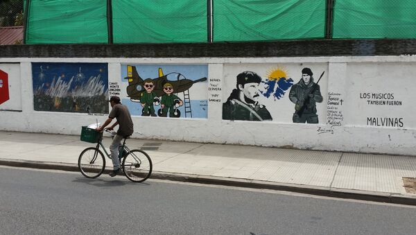 A man cycles past a mural about the Malvinas War on the wall of a military base in Buenos Aires - Sputnik International