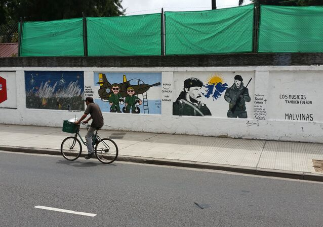 A man cycles past a mural about the Malvinas War on the wall of a military base in Buenos Aires