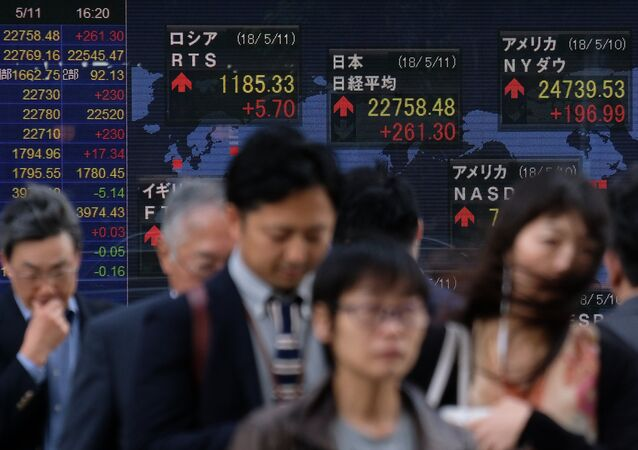 Pedestrians walk past a stock indicator showing share prices of the Tokyo Stock Exchange (top-C) and other overseas stock markets in Tokyo on May 11, 2018
