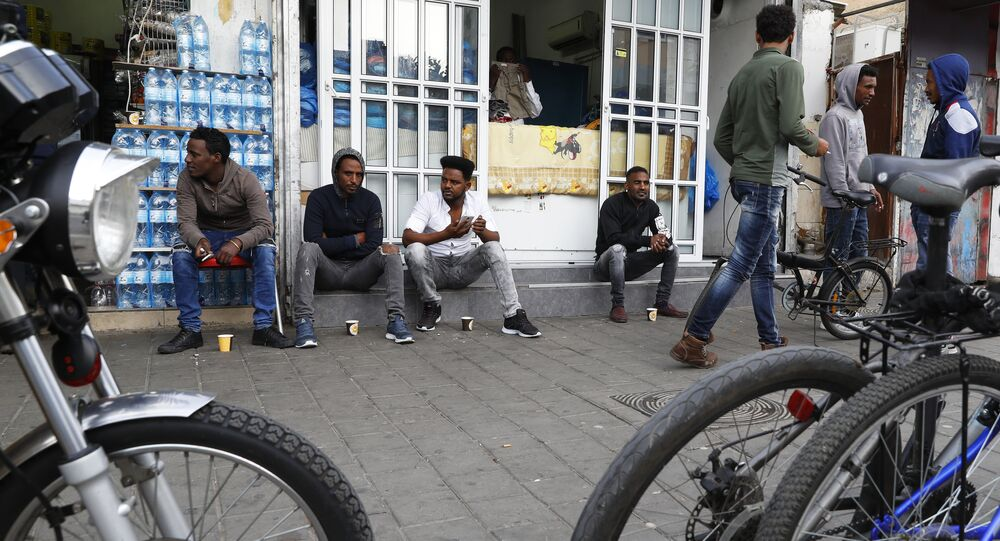 African immigrants from Eritrea sit in the street in the southern district of the Israeli city of Tel Aviv on April 5, 2018