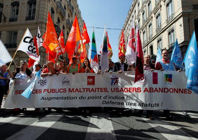 French civil servants carry labour union flags as they march behind a banner during a national day of strikes by public sector workers, in Lyon, France, May 22, 2018