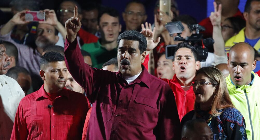 Venezuela's President Nicolas Maduro raises a finger as he is surrounded by supporters while speaking during a gathering after the results of the election were released, outside of the Miraflores Palace in Caracas, Venezuela, May 20, 2018