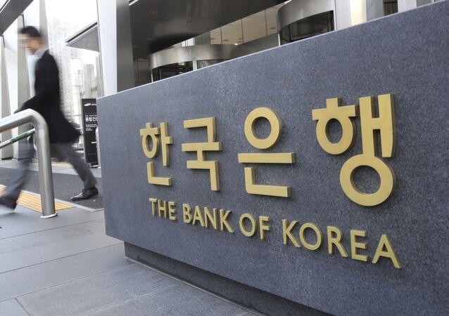 A man walks by the sign of the Bank of Korea in Seoul, South Korea, Thursday, Nov. 30, 2017