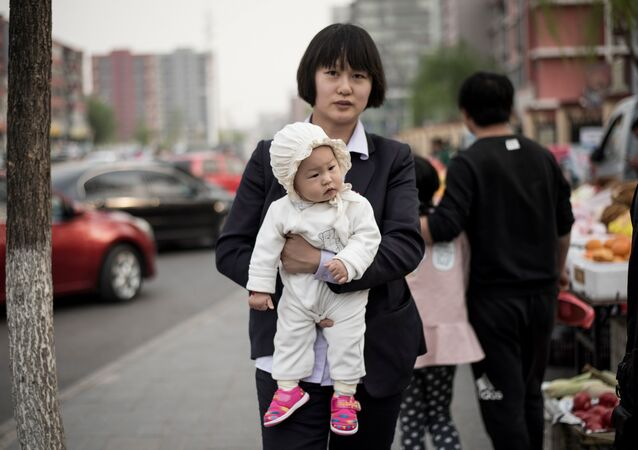 A mother holds her baby as she walks in a market in Shunyi on the outskirts of Beijing on April 13, 2017