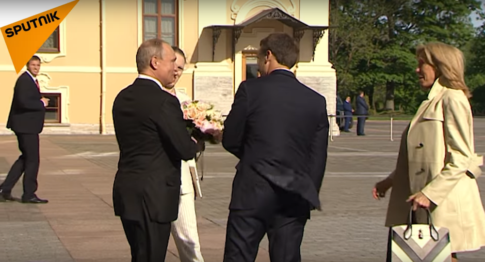 Putin giving flowers to the French First Lady, May 24, 2018
