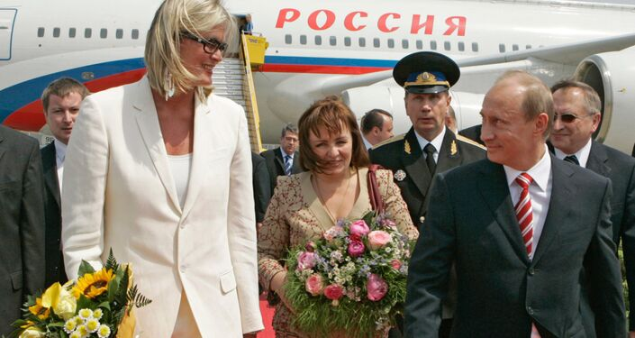 Austrian Foreign Minister Ursula Plassnik (left) holds her sunflower bouquet, with Russian President Vladimir Putin and his wife Lyudmila walking alongside her after meeting at Vienna's airport