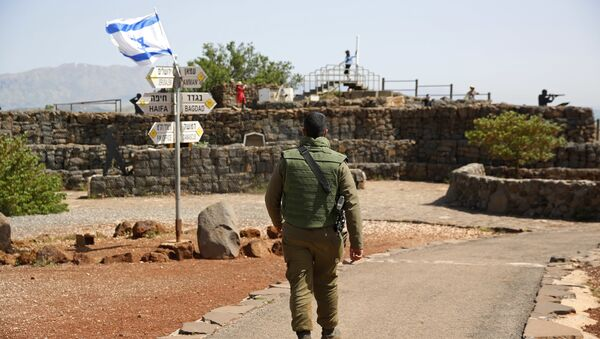An Israeli soldier walks in an old military outpost, used for visitors to view the Israeli controlled Golan Heights, near the border with Syria, Thursday, May 10, 2018 - Sputnik International