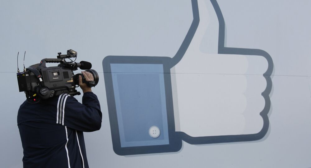 A television photographer shoots the Like sign outside of Facebook headquarters in Menlo Park, Calif