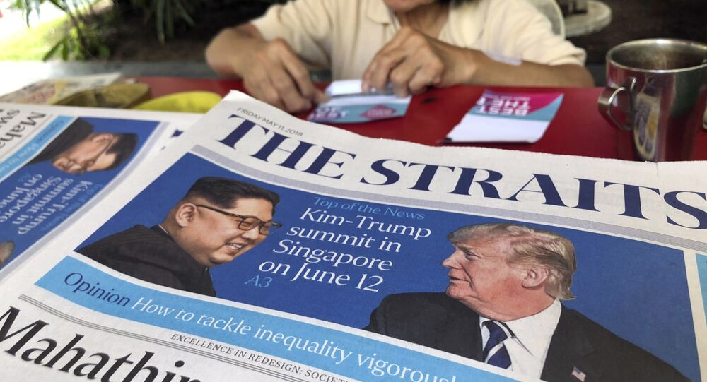 FILE - In this May 11, 2018, file photo, a news vendor counts her money near a stack of newspapers with a photo of U.S. President Donald Trump, right, and North Korea's leader Kim Jong-un on its front page in Singapore.