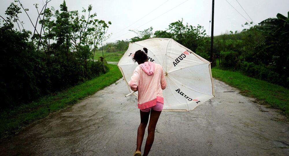 Dalma Samora, 14, walks against the winds of Subtropical Storm Alberto as it passes by the west coast of Cuba, in La Palma, Cuba, May 26, 2018.