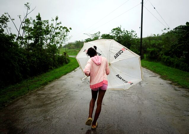 Dalma Samora, 14, walks against the winds of Subtropical Storm Alberto as it passes by the west coast of Cuba, in La Palma, Cuba, May 26, 2018.