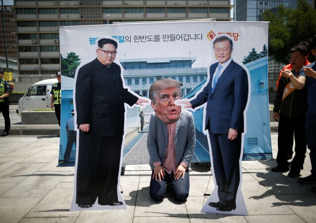 A man wearing a mask of U.S. President Donald Trump kneels down between cutouts of North Korean leader Kim Jong Un and South Korean President Moon Jae-in during an anti-U.S. President Donald Trump rally near U.S. embassy in Seoul, South Korea, May 25, 2018