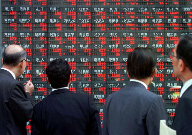 Japanese businessmen stop in front of an electronic board flashing share prices in downtown Tokyo (File)