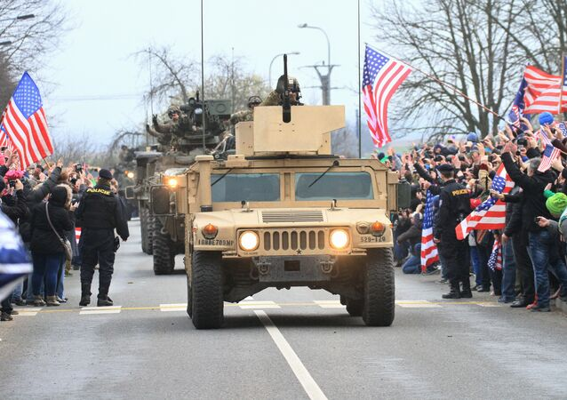 People greet a US military convoy, including Humvees, arriving at the Military School in Vyskov, South Moravia after entering the Czech Republic on March 29, 2015
