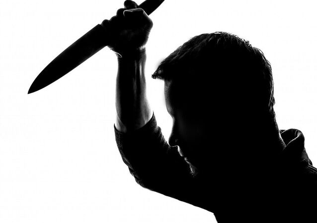 A silhouette of a man holding a knife