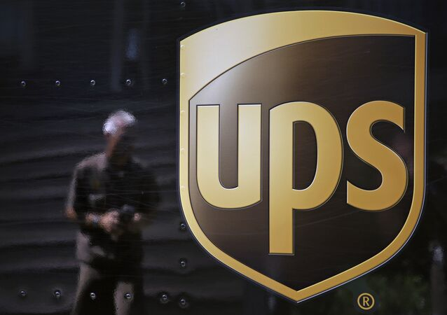 In this June 20, 2014, file photo, the United Parcel Service logo is seen on the side of a truck as driver Marty Thompson is reflected returning from a delivery in Cumming, Ga.