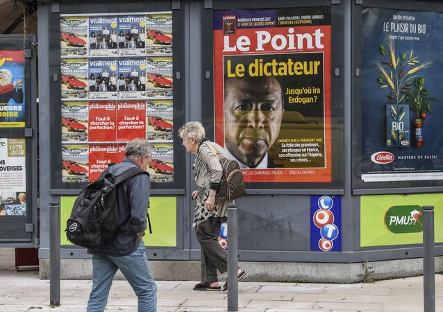 A man walks by a storefront displaying the front page of French news magazine Le Point showing a picture of Turkish president and reading the dictator, on 30 May, 2018 in Valence