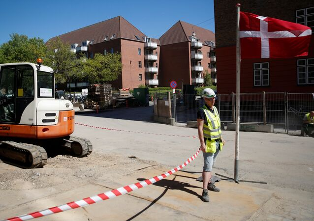 A worker stands beside a Danish flag on a construction site of new housing being built next to Mjolnerparken, a housing estate that features on the Danish government's Ghetto List, in Copenhagen, Denmark, May 8, 2018