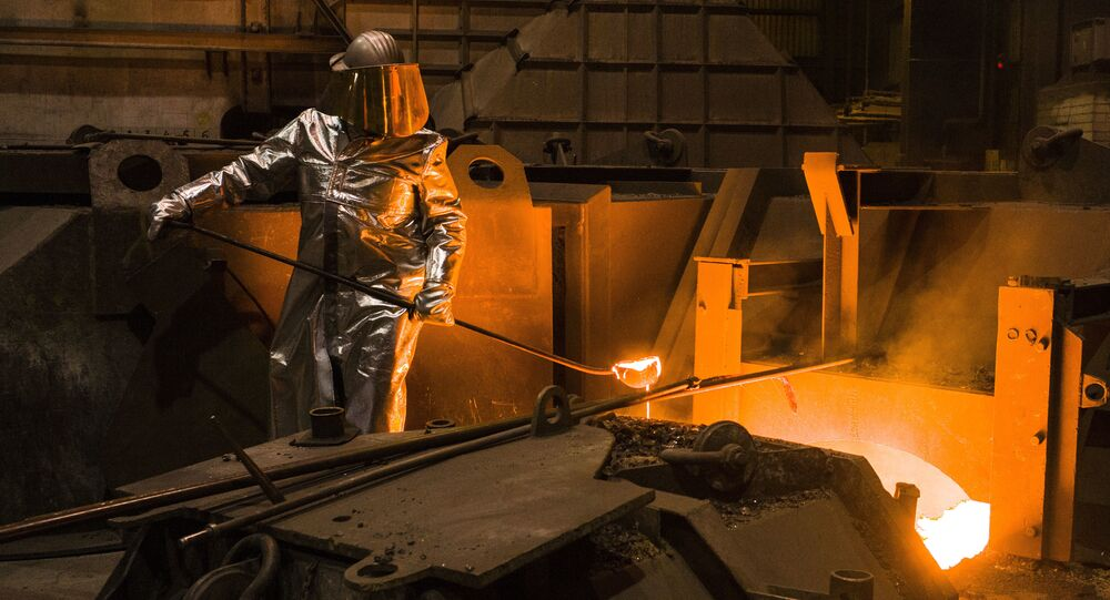 An employee in protective clothing takes a sample from the furnace at the steel producer, Salzgitter AG, in Salzgitter, Germany, Thursday, March 22, 2018