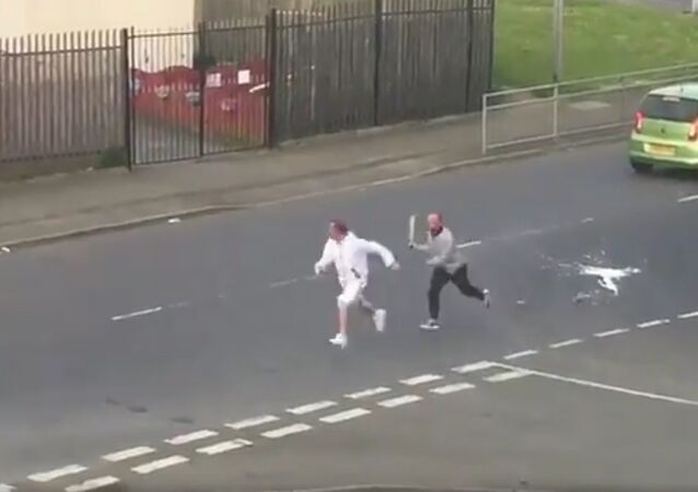 A man wielding a sword chasing another man down a road in Glasgow