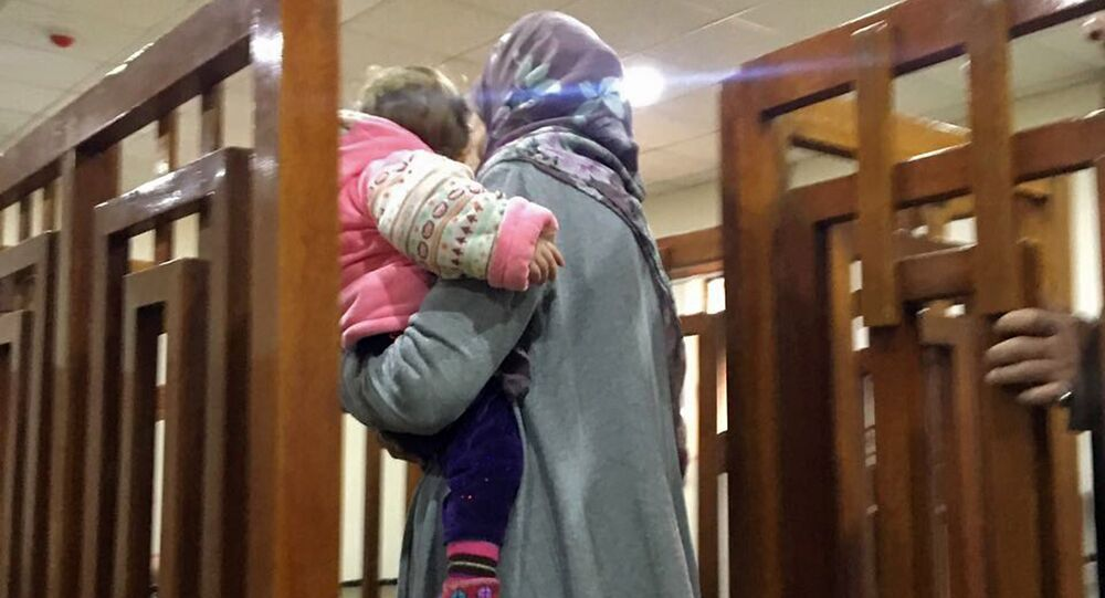 This file photo taken on February 19, 2018, shows French Jihadist Melina Boughedir carrying her son as she arrives to court in the Iraqi capital Baghdad
