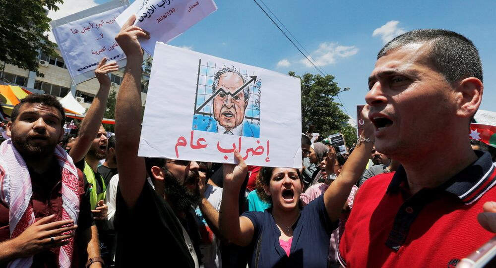 A Jordanian protester holds a picture of Jordanian Prime Ministers Hani al-Mulki and chants slogans during a strike against the new income tax law, in Amman, Jordan May 30, 2018