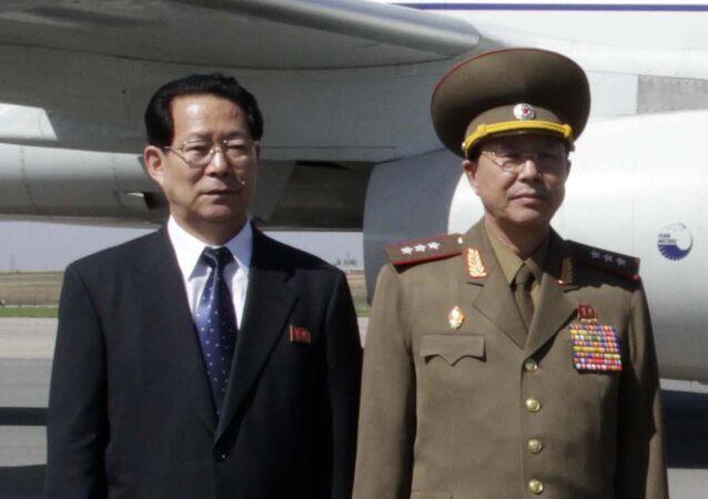 Ri Yong Gil, right, poses at Pyongyang Airport in 2013.