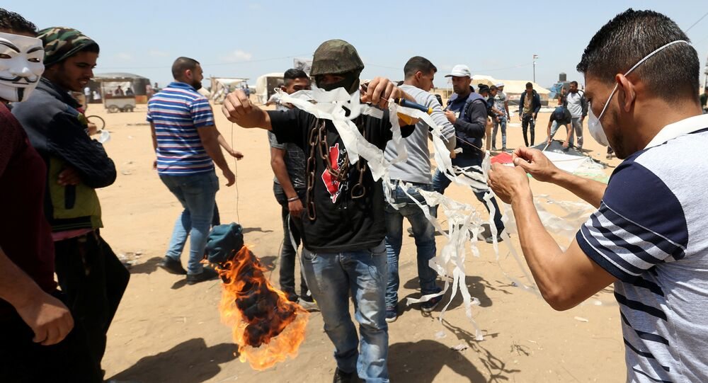 Palestinian demonstrators prepare to set a kite on fire to be thrown at the Israeli side during a protest demanding the right to return to their homeland, at the Israel-Gaza border in the southern Gaza Strip, May 11, 2018