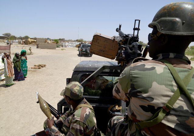 (File) A photo taken on May 25, 2015 shows Nigerien soldiers patroling on a road between Diffa and Bosso