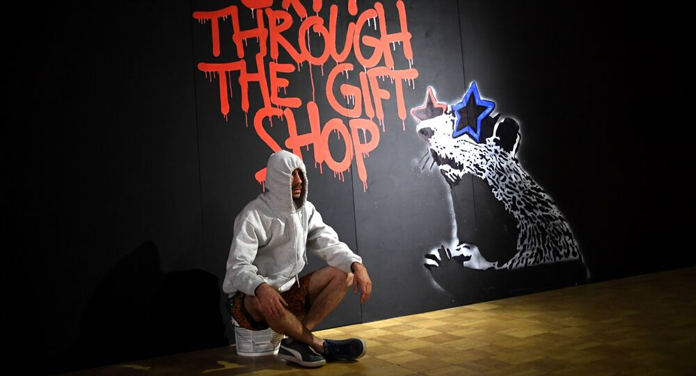 A visitor during an early show of the exhibition of English street artist Banksy at the Central House of Artist