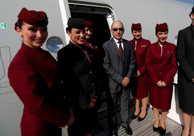 Qatar Airways Chief Executive Officer Akbar al-Baker poses with cabin crew in an Airbus A350-1000 at the Eurasia Airshow in the Mediterranean resort city of Antalya, Turkey April 25, 2018