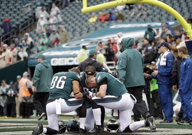 Philadelphia Eagles Zach Ertz (86), Carson Wentz (11), and Trey Burton (88) pray ahead of an NFL football game against the San Francisco 49ers, Sunday, Oct. 29, 2017, in Philadelphia.