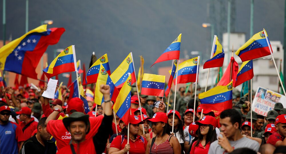 Civilians hold Venezuelan flags as they walk in a parade during a military exercise in Caracas, Venezuela, August 26, 2017