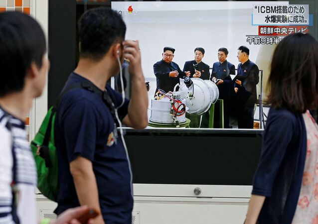 People walk past a street monitor showing North Korea's leader Kim Jong-Un in a news report about North Korea's nuclear test, in Tokyo, Japan, September 3, 2017