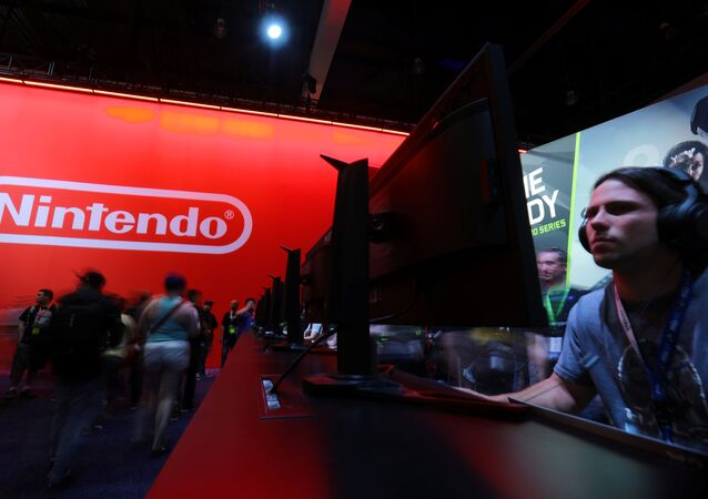 An attendee plays a video game next to the Nintendo booth at the E3 2017 Electronic Entertainment Expo in Los Angeles, California, U.S. June 13, 2017