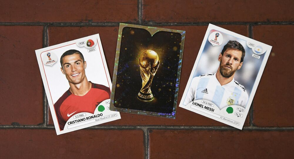 This photo taken on April 20, 2018 shows collectible cards featuring (L-R) Portugal's forward Cristiano Ronaldo, the Fifa World Cup Trophy and Argentina's forward Lionel Messi as part of a series featuring players for the 2018 Russia football World Cup at the Panini Group factory in Modena, northern Italy