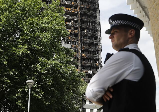 A police officer stands near to the burnt Grenfell Tower apartment building standing testament to the recent fire in London, Friday, June 23, 2017.