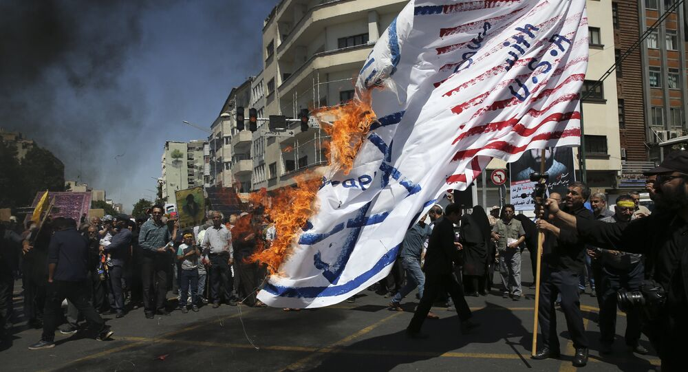 Iranian protesters burn a representation of the U.S. and Israeli flags in their annual anti-Israeli Al-Quds, Jerusalem, Day rally in Tehran, Iran, Friday, June 8, 2018